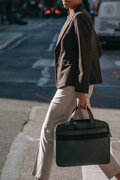 Anonymous elegant ethnic businesswoman with laptop bag walking on zebra crossing
