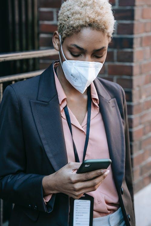 Stylish black female manager using smartphone on street