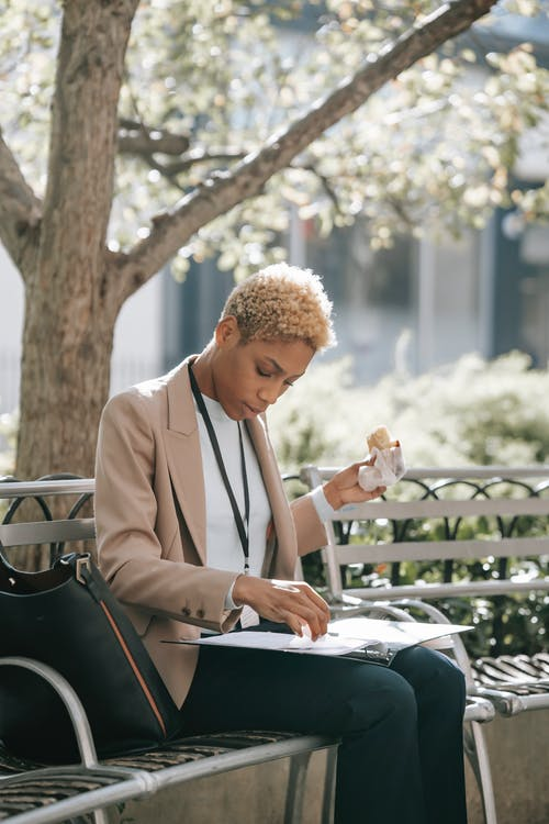 Concentrated young African American female employee with short blond hair in formal outfit sitting on bench in city park and reading documents during lunch break