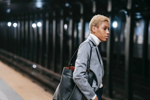 Calm elegant young black lady standing on platform in underground