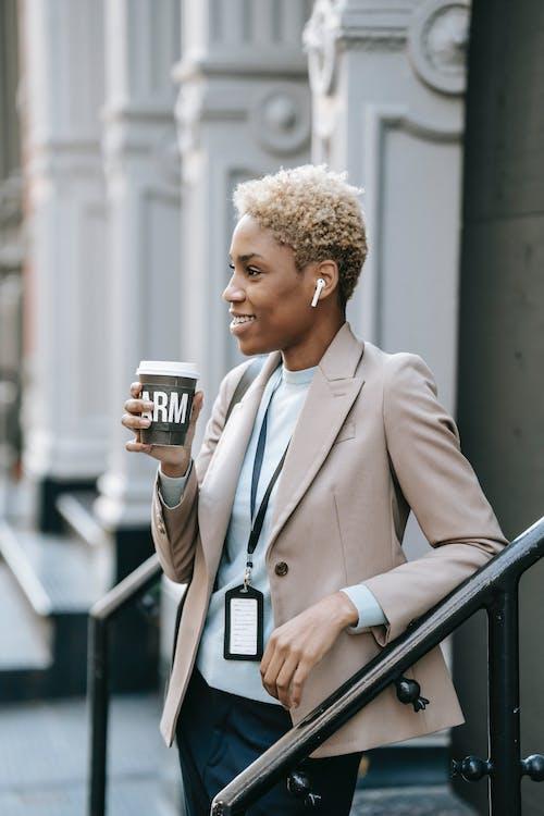 Positive young black female entrepreneur in wireless earphones drinking takeaway coffee on street