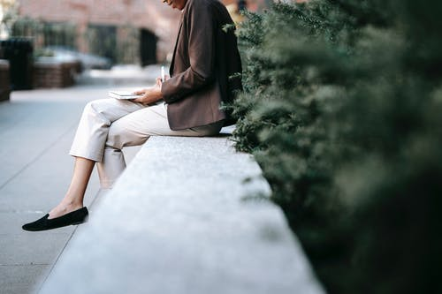 Side view of crop unrecognizable young ethnic female employee in classy outfit sitting on stone border in city park and taking notes in planner