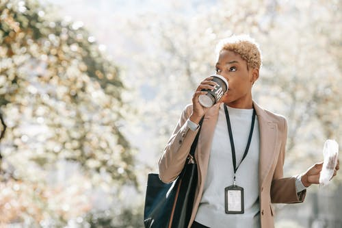 Young African American businesswoman drinking takeaway beverage during coffee break in park