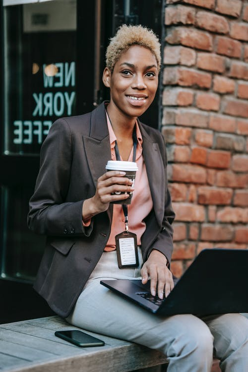Smiling confident young African American female employee in formal clothes and name tag sitting on bench on city street with cup of takeaway coffee and working on laptop