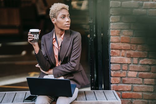 Dreamy young ethnic female manager in classy outfit drinking takeaway coffee and looking away thoughtfully while sitting on bench on city street with laptop during break