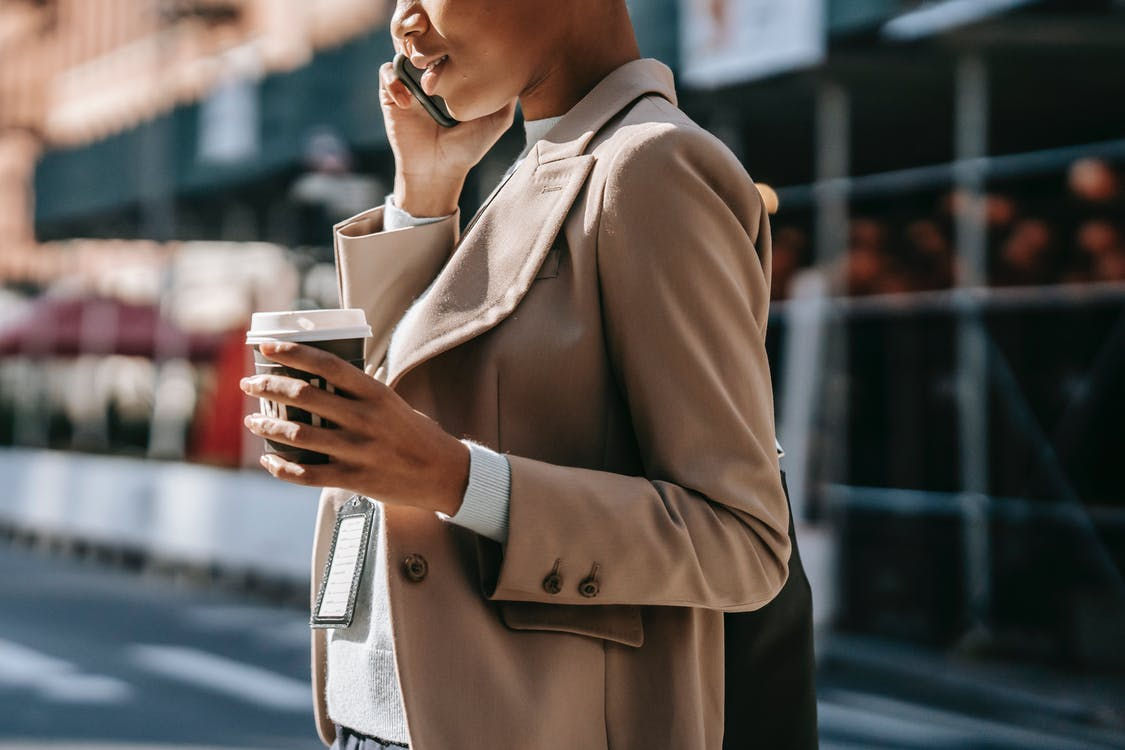 Crop black businesswoman speaking on smartphone on street