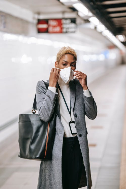 Young African American female in stylish formal wear putting on protective mask while waiting for train on underground platform