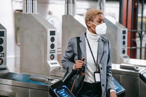 Calm attractive African American female in stylish formal wear and protective mask passing through turnstile gates in underground station