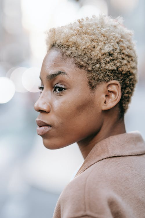 Calm black woman standing on blurred street