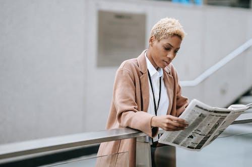 Focused black businesswoman reading newspaper on street