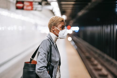 Pensive black woman in mask standing on railway platform
