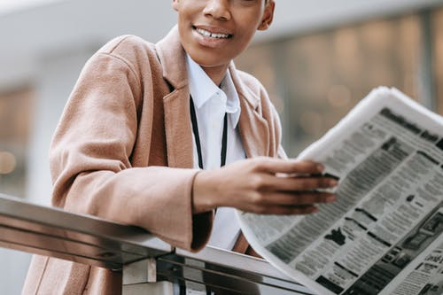 Smiling Woman in Brown Coat Holding Newspaper
