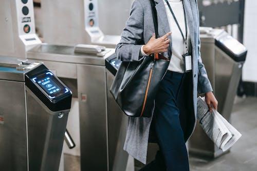 Man in Black Coat and Blue Denim Jeans Standing Beside Gray Metal Railings