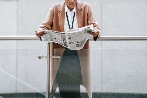 Woman in Pink Blazer Reading Newspaper
