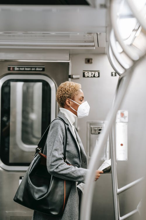 Man in White Face Mask and Gray Jacket in Train