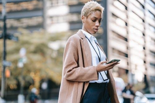 Man in Brown Coat Holding Smartphone