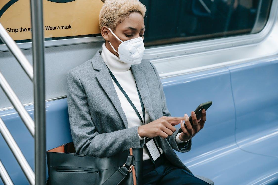 Crop black focused woman using smartphone in metro train