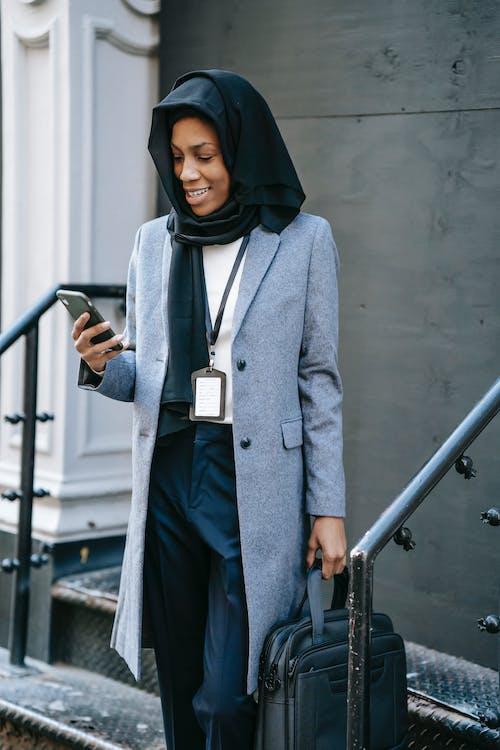 Woman in Gray Coat Standing Beside Gray Metal Railings