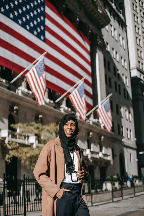 Woman in Brown Hijab Standing Near Us Flag