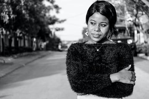 Black and white of African American female in trendy elegant outfit looking away on blurred background of street