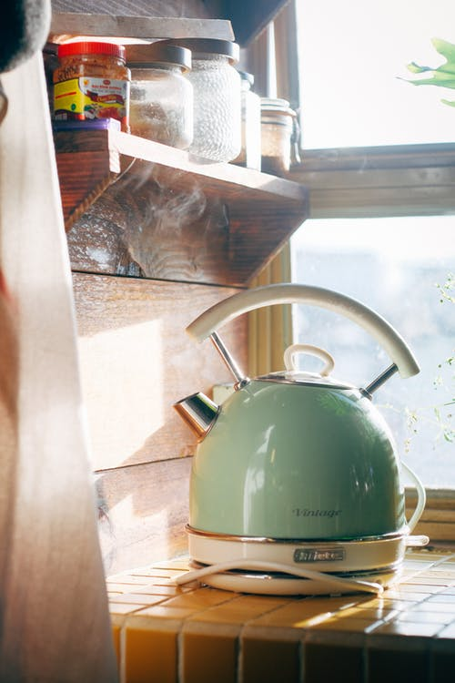 Green and Silver Kettle on Brown Wooden Table