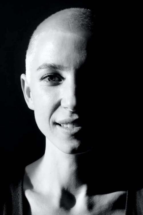 Black and white of crop young female with shaved blond hair looking at camera while smiling in studio
