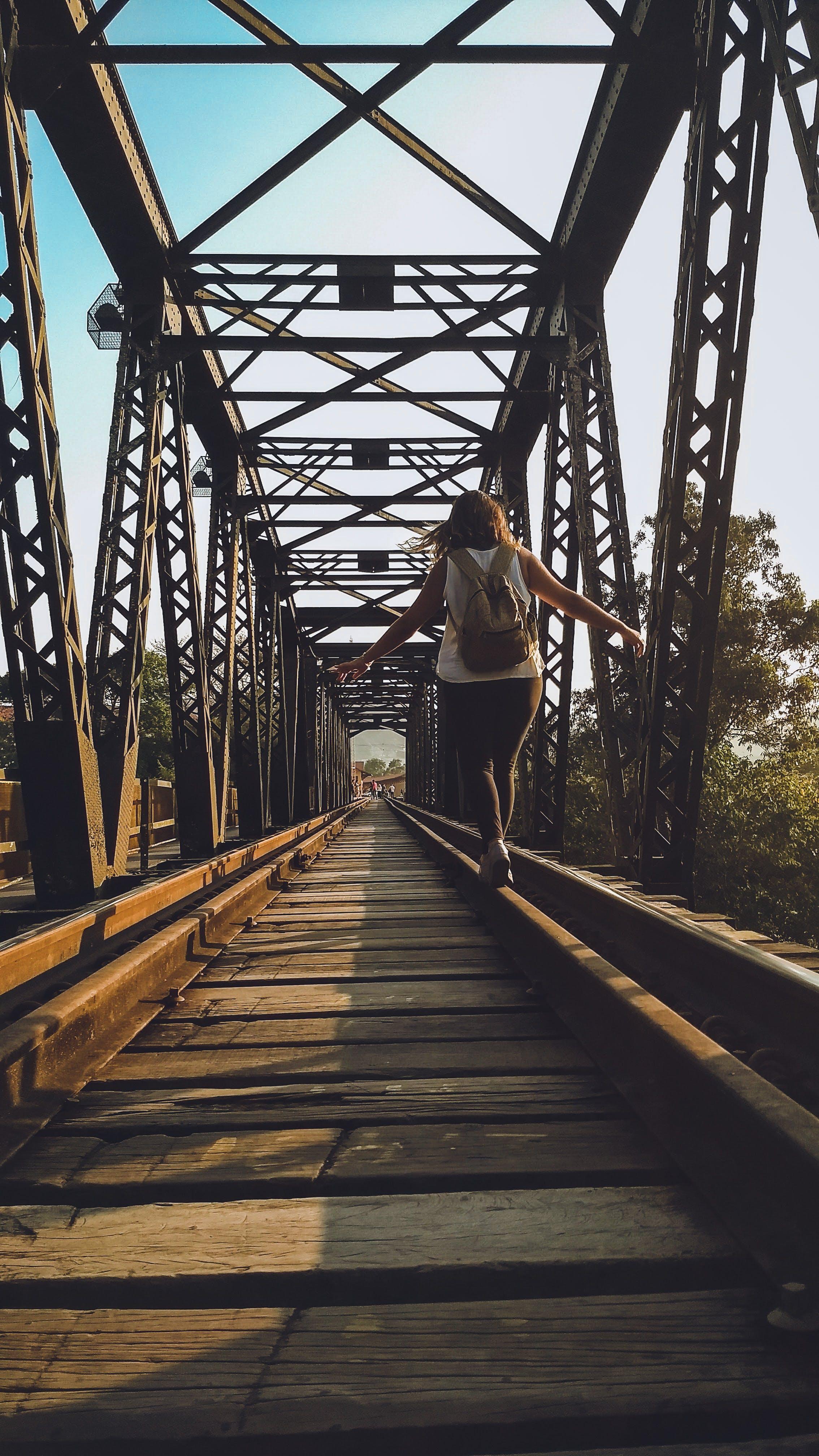 Woman Walking on a Train Rail