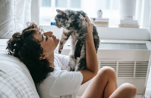 Content woman with cat at home