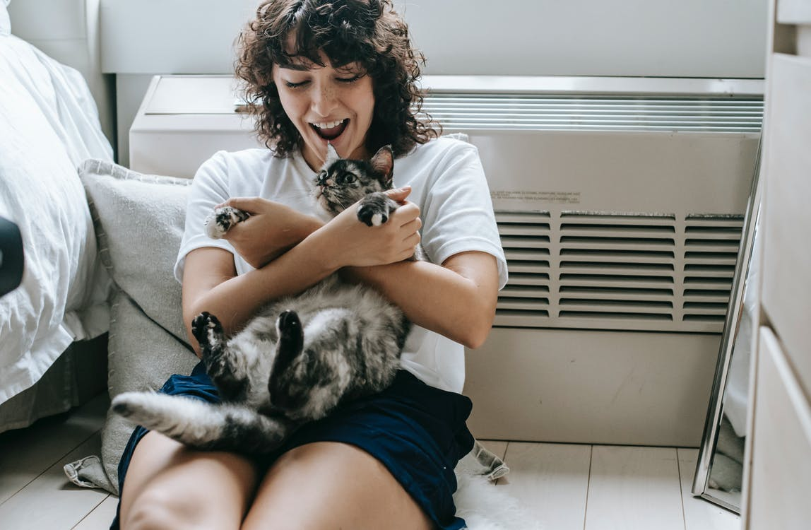 Happy female with dark hair caressing adorable dappled cat while sitting on floor with hands crossed near radiator and bed in room at home