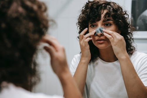 Calm woman applying skincare product on face