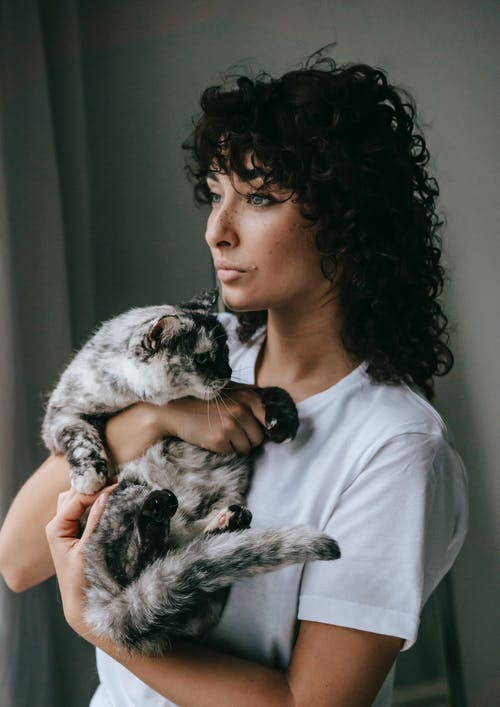 Pensive woman with fluffy cat on hands