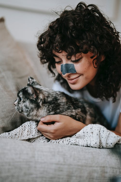 Positive young woman with curly dark hair and charcoal cleansing strip on nose smiling and playing with soft purebred cat