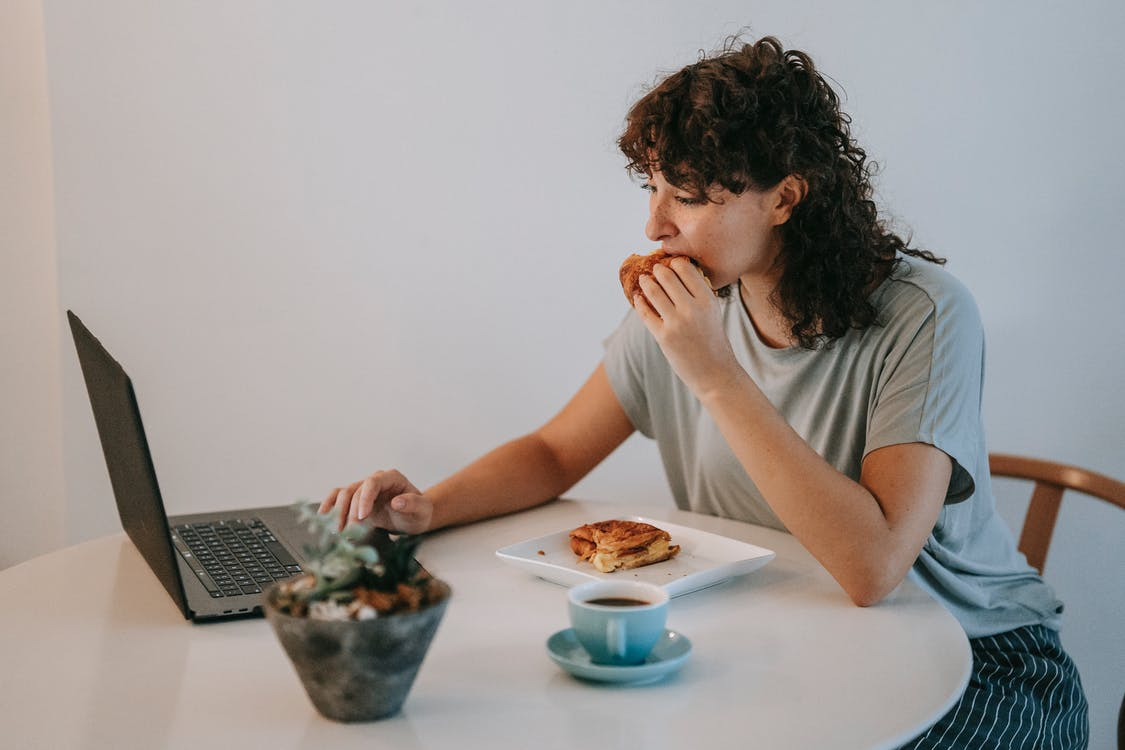 Young female with curly dark hair working with netbook while looking at screen and eating toasts with cup of coffee