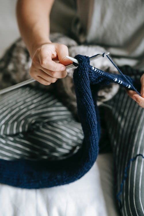 From above of crop anonymous woman in casual clothes knitting warm cloth with needles and yarn while relaxing on bed at home with calm lazy cat
