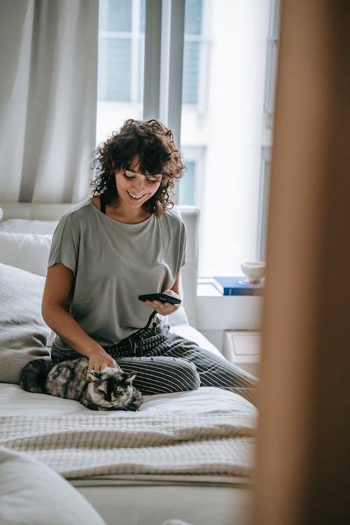 ベッドに座っている灰色の乗組員の首のtシャツの女性