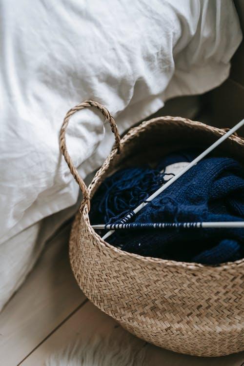在白色纺织品上的棕色编织的篮子