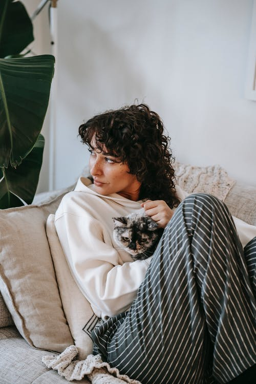 Adult contemplative female embracing cute cat while sitting on soft couch and looking away in living room
