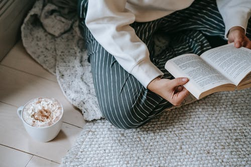 Female reading book while drinking coffee with whipped cream