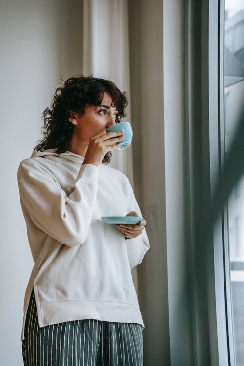 Low angle of female in casual wear drinking hot coffee in morning standing near panoramic window
