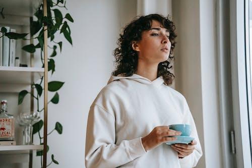 Wanita Berkemeja Putih Lengan Panjang Memegang Mug Keramik Biru
