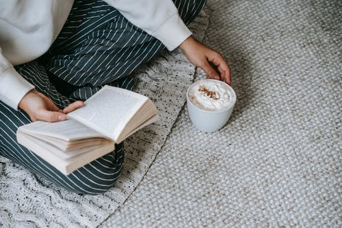 From above of crop anonymous female sitting with crossed legs and reading book with mug of coffee with whipped cream while resting at home