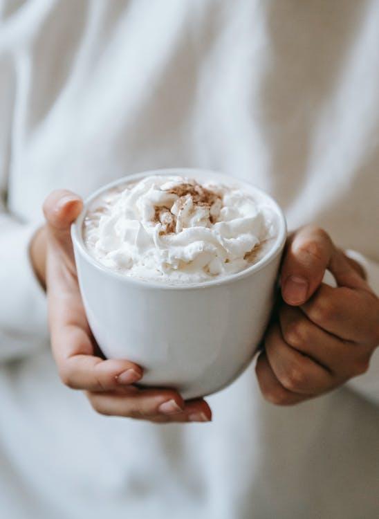 白いクリームと白いセラミックカップを持っている人