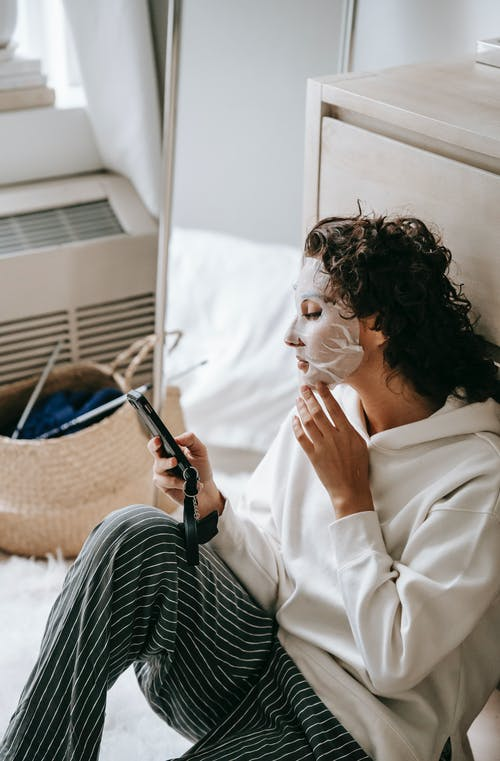 High angle of female surfing Internet while doing beauty procedure with moisturizing sheet mask at home