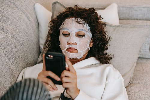 Woman in hydrating sheet mask browsing smartphone