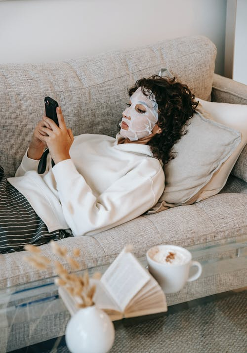 Young woman in face mask using smartphone on sofa