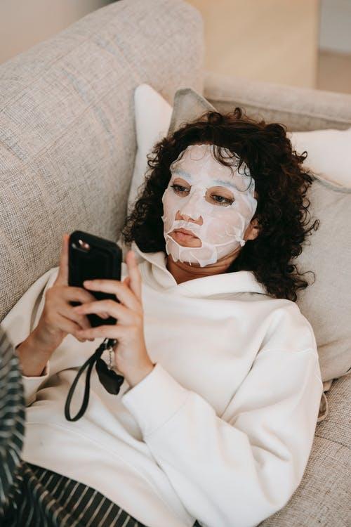 From above of female in moisturizing beauty mask applied on face lying on couch and browsing cellphone