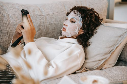 Side view of female wearing facial moisturizing mask surfing cellphone while lying on couch in living room during skincare routine
