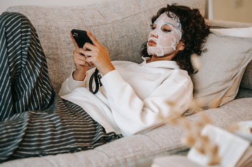 Focused woman with cosmetic mask browsing phone