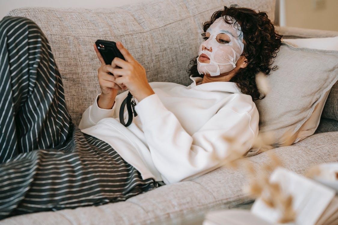 Frau In Der Weißen Robe, Die Auf Bett Liegt, Das Schwarzes Smartphone Hält