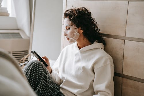 Calm woman in mask texting on smartphone
